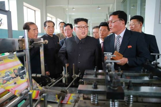김정은 북한 노동당 위원장이 상이군인들이 근무하는 낙랑영예군인수지일용품공장을 방문해 생산라인을 돌아보고 있다. [노동신문]