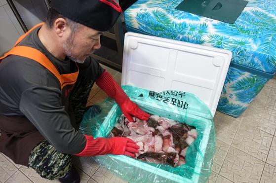 주인 홍탁근씨가 부산수협 다대포공판장에서 경매 받아 내장 분리하고 초벌 손질해 얼음 채워 보낸 상자를 열어 아귀를 살펴보고 있다.