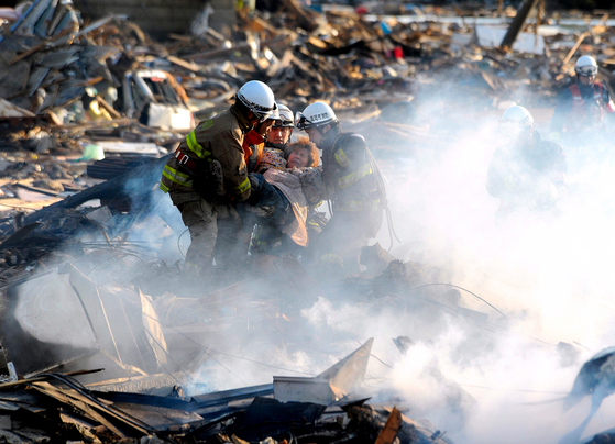 A resident is rescued from debris in Natori, Miyagi, northern Japan Saturday, March 12, 2011 after one of the country's strongest earthquakes ever recorded hit its eastern coast on Friday. (AP Photo/Asahi Shimbun, Noboru Tomura) JAPAN OUT, NO SALES, MANDATORY CREDIT