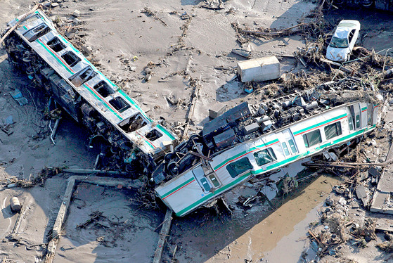 Cars of a train lie overturned in Shinchi town, Fukushima prefecture, Saturday, March 12, 2011 after being washed away by an earthquake-triggered tsunami. The powerful tsunami created by one of the strongest earthquakes ever recorded swept away Japan's east coast Friday. (AP Photo/Kyodo News) MANDATORY CREDIT, NO LICENSING ALLOWED IN CHINA, HONG KONG, JAPAN, SOUTH KOREA AND FRANCE