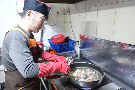 아귀수육을 조리하면서 끓는 밑국물에 살을 넣은 다음 가위로 위를 잘라 넣는 주인 홍탁근씨.