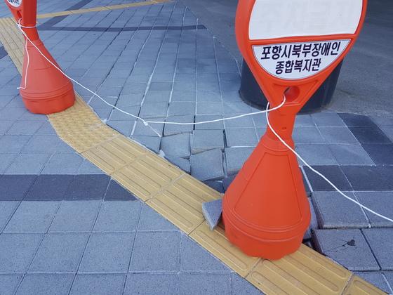 포항시북부장애인종합복지관 입구 근처 바닥이 지진으로 뒤틀려 있다. 피해를 입은 부분은 내진 설계에 포함되지 않는 곳이고, 왼쪽의 멀쩡한 부분은 내진 설계가 적용된 곳이다. 송우영 기자