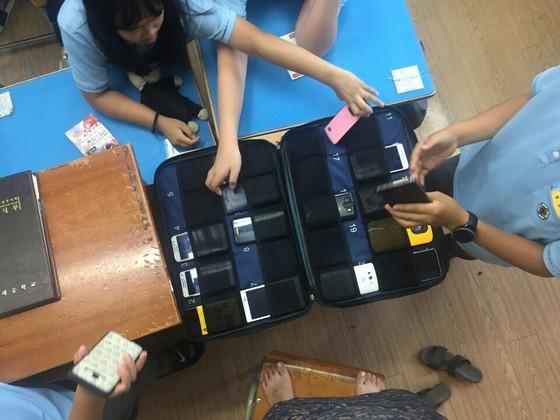 수업 시작 전 조례시간에 휴대전화를 제출하고 있는 학생들. [중앙포토]