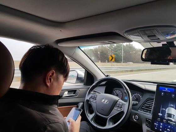 자율주행차 운전석에 앉은 연구원이 자동주행모드로 전환한 후 핸들에서 손을 떼고 휴대폰을 보고 있다. 함종선 기자