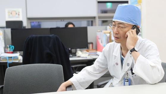 지난 17일 이국종 아주대의대 교수가 전화를 받고 있다. 이 교수는 지난 13일 귀순 과정엣더 중상을 입은 북한군을 수술했다. 그는 국내 최고의 총상 전문가다. 김춘식 기자