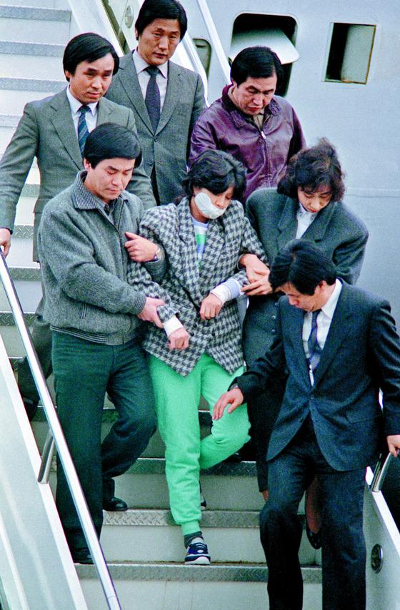 1987년 대한항공(KAL) 858기 폭파사건 용의자로 체포된 김현희(당시 25세)가 그해 12월 15일 흰색 마스크를 쓴 채 호송요원들의 부축을 받으며 서울 김포공항을 통해 입국하고 있다. [중앙포토]