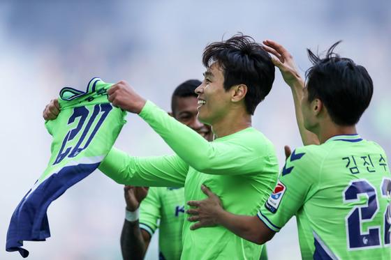 """이동국은 29일 관중석을 향해 자신의 유니폼의 이름을 펼쳐보이는 세리머니를 했다. 스페인 바르셀로나 메시가 지난 4월 레알 마드리드전 득점 후 유니폼을 펼쳐든 세리머니와 비슷했다. 이동국은 """"전북 입단 후 홈팬들이 열정적으로 지지해줘 이 자리에 있을 수 있었다. 홈팬들에게 제 이름을 다시 한번 보여주고 싶었다""""고 말했다. [사진 프로축구연맹]"""