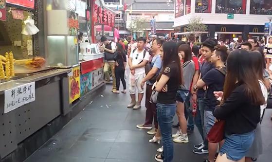 중국 선전 거리의 오징어 꼬치를 굽는 가게 앞에 사람들이 줄을 서서 기다리고 있다. [사진 김민철]
