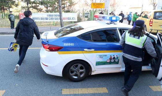 대학수학능력시험일인 23일 경북 포항시 남구 오천읍에 있는 수능 시험장인 포은중학교에서 한 수험생이 경찰차를 타고 도착하고 있다. [연합뉴스]