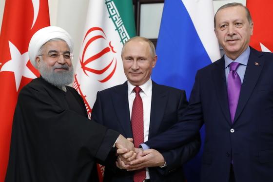 22일(현지시간) 러시아 소치에서 열린 시리아 사태 중재 정상회의에서 손을 맞잡은 하산 로하니 이란 대통령, 블라디미르 푸틴 러시아 대통령, 레제프 타이이프 에르도안 터키 대통령(왼쪽부터). [타스=연합뉴스]