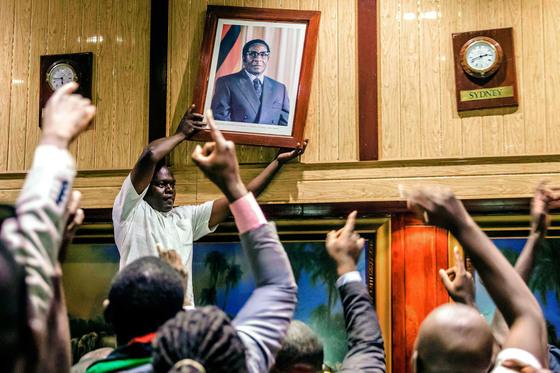 21일(현지시간) 짐바브웨 수도 하라레의 대통령 집무실에서 시민들이 벽에 걸린 로버트 무가베 전 대통령의 초상화를 치우며 환호하고 있다. 37년간 집권한 무가베는 이날 사임했다. [AFP=연합뉴스]