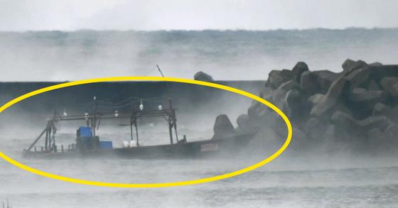 24일 일본 아키타(秋田)현 유리혼조시(由利本莊市) 해안의 방파제에 표류해 있는 북한 선적 추정 목선. 일본 언론들은 전날 이 배와 북한 국적 추정 남성 8명이 발견돼 경찰이 조사 중이라고 보도했다. [아키타 교도=연합뉴스]