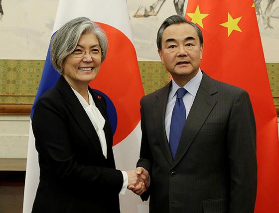 강경화 외교부 장관(왼쪽)이 22일 베이징 댜오위타이 국빈관에서 열린 한·중 외교장관 회담에서 왕이 중국 외교부장과 악수를 하고 있다. [EPA=연합뉴스]