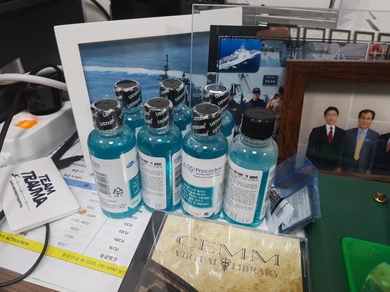 이 센터장은 피로와 스트레스에 시달리는데, 구강 염증을 예방하기 위해 가글을 쌓아놓고 쓴다. 오른쪽에는 '아덴만의 영웅' 석해균 선장과 찍은 사진이 놓여 있다. 신성식 기자