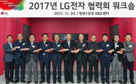 """조성진 LG전자 대표이사(왼쪽 여섯번째)는 24일 창원R&D센터에서 열린 '2017년 LG전자 협력회 워크숍'에서 """"지능형 자율 공장을 모든 제조 부문에 확대하겠다""""고 강조했다. 사진은 행사에 참석한 한주우 LG전자 글로벌생산부문장(왼쪽 여덟번째), 이시용 구매센터장(왼쪽 세번째) 등 LG전자 경영진과 주요 협력사 대표들이 손을 맞잡은 모습. [사진 LG전자]"""