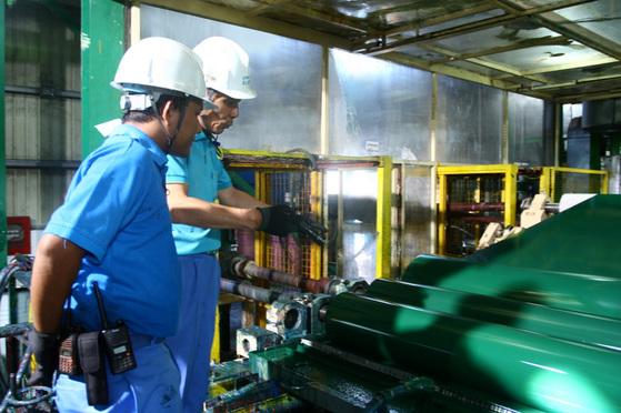 미얀마 양곤에 위치한 미얀마포스코 공장 직원들이 생산라인에서 나온 컬러강판의 품질을 확인하고 있다 . [사진 포스코그룹]