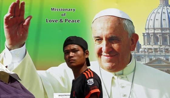 프란치스코 교황의 미얀마 방문을 환영하는 포스터 앞을 지나가는 한 남성. [EPA=연합뉴스]