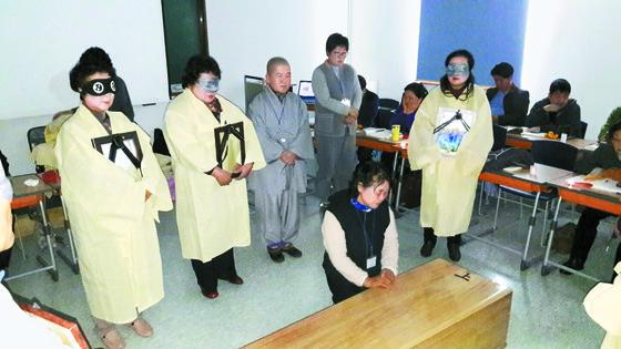 '웰다잉 지도사' 교육생들이 입관 체험을 하고 있다. 상복을 입은 이들이 망자 체험자다.  [사진제공=의성군]