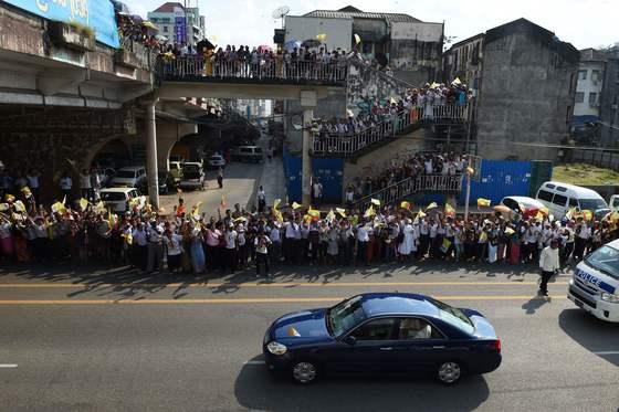 27일 미얀마 양곤에서 프란치스코 교황이 탄 차가 지나가자 시민들이 환호하고 있다. 교황이 미얀마를 방문한 것은 이번이 처음이다. [AFP=연합뉴스]