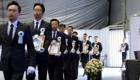 지난 2014년 5월 1일 오전 경기도 안산시 화랑유원지에 마련된 세월호 사고 희생자 정부 합동분향소에서 장례진행 요원들이 희생자들의 영정사진을 옮기고 있다. 사진공동취재단