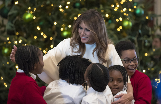 도널드 트럼프 미국 대통령 부인 멜라니아 트럼프 여사가 27일(현지시각) 크리스마스 장식 공개 행사에 참여한 아이들을 안아주고 있다. [AP=연합뉴스]