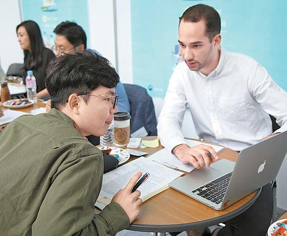 해외 취업 박람회를 찾은 학생이 해외 취업 준비를 위해 영문 이력서 작성 방법에 대해 듣고 있다.