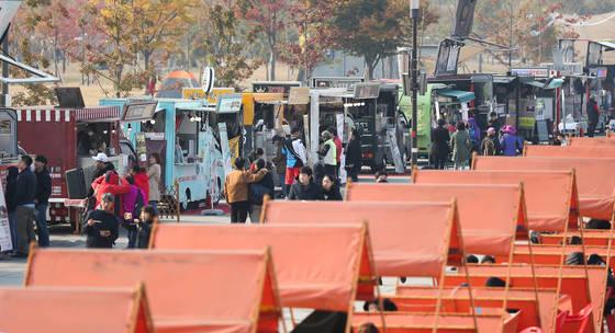 [서울=연합뉴스] 서울 여의도 한강공원에서 열린 '서울 푸드트럭의 날' 행사에서 시민들이 음식을 고르고 있다. <저작권자(c) 연합뉴스, 무단 전재-재배포 금지>