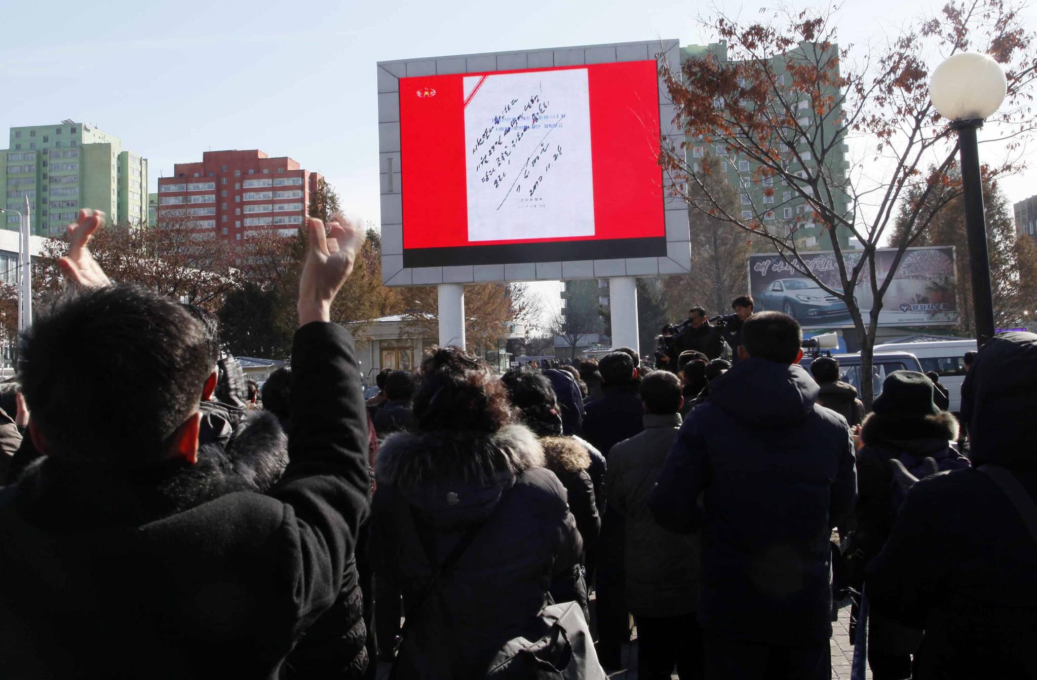 북한 평양 시민들이 29일 낮 시내에서 조선중앙TV의 화성15형 시험발사 보도를 지켜보고 있다. 화면에는 김정은의 화성15형 시험발사 승인 사인이 보인다.[AP=연합뉴스]