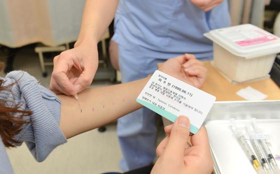이수민(27)씨가 세브란스병원 지역의약품안전 센터에서 알레르기 원인을 찾기 위해 피부 검사를 받고 있다. 센터에서는 원인 약물 정보가 적힌 카드를 발급해준다. [사진 세브란스병원]