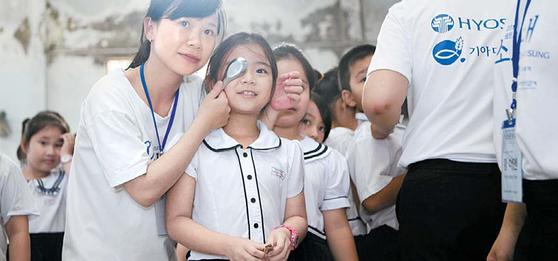 효성 해외의료봉사단 미소원정대의 의료진이 베트남 어린이의 시력을 측정하고 있다. 미소원정대는 지난 2011년부터 스판덱스와 타이어코드를 생산하는 베트남 동나이성에서 무료 진료를 실시하고 있다. 약 9000명에게 혜택을 제공했다. [사진 효성그룹]