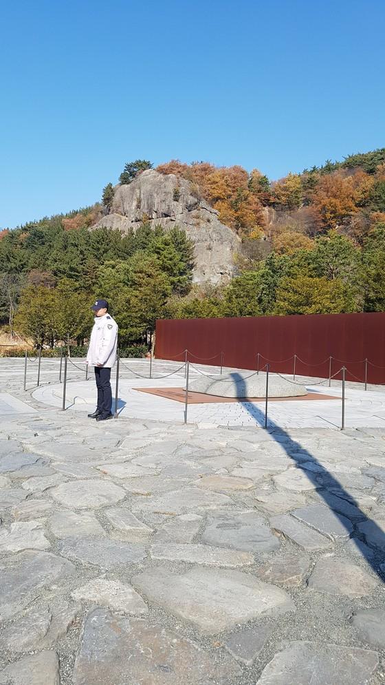 노무현 전 대통령의 묘역. 1만6000개의 박석에 1만8000여명의 추모글이 쓰여 있다. 뒤편에 보이는 것이 부엉이바위다. 김진국 기자