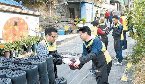 에쓰-오일은 지역사회에 나눔을 실천하고 있다. 에쓰-오일 오스만 알 감디(왼쪽) CEO와 본사 임직원 자원봉사단원들이 서울 서대문구 홍제동 개미마을에서 사랑의 연탄나눔을 하고 있다. [사진 에쓰-오일]