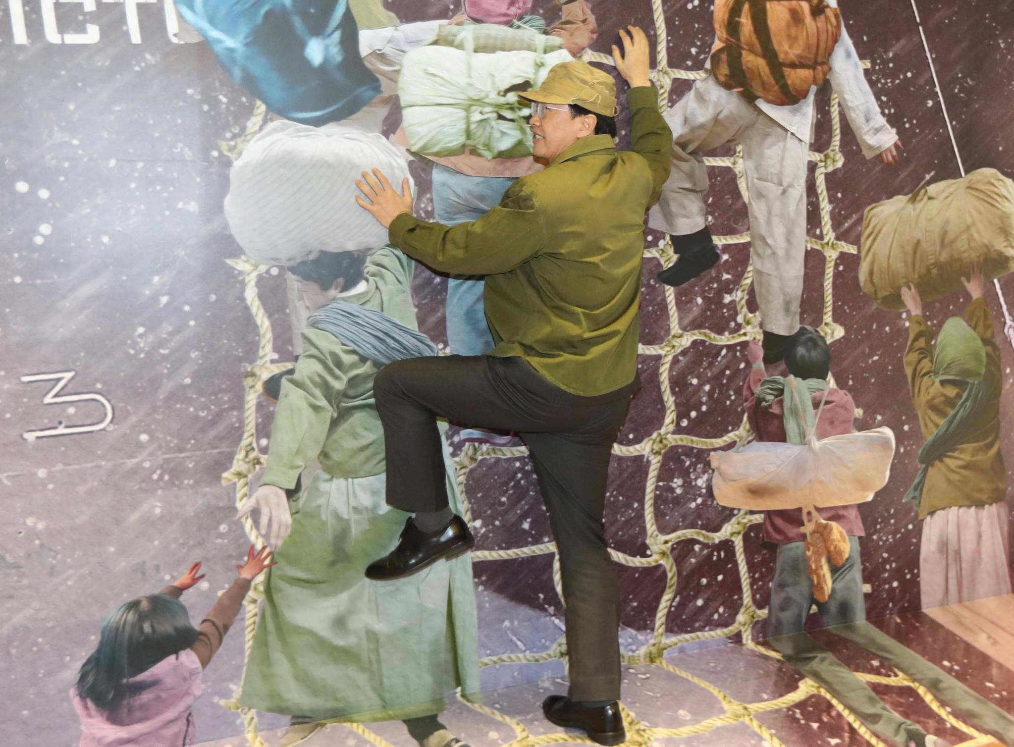 조명균 통일부 장관이 흥남철수 당시 모습을 재현한 그림 앞에서 피난민 복장을 하고 배에 오르는 모습을 보여주고 있다. 신인섭 기자