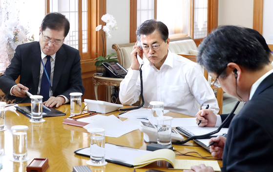 문재인(가운데) 대통령이 29일 오전 청와대에서 북한의 신형 ICBM '화성-15형' 발사와 관련해 도널드 트럼프 미국 대통령과 전화로 대응 방안을 논의하고 있다. 왼쪽은 정의용 국가안보실장. [사진제공=청와대]