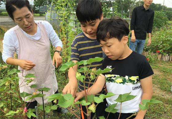 농촌진흥청이 시범 운영한 치유농업 프로그램의 하나로 경북 경산시 뜨락에서 원예치유과정이 운영됐다. 교육과정에 참여한 어린이들이 화초를 만져보고 있다. [사진 농촌진흥청]