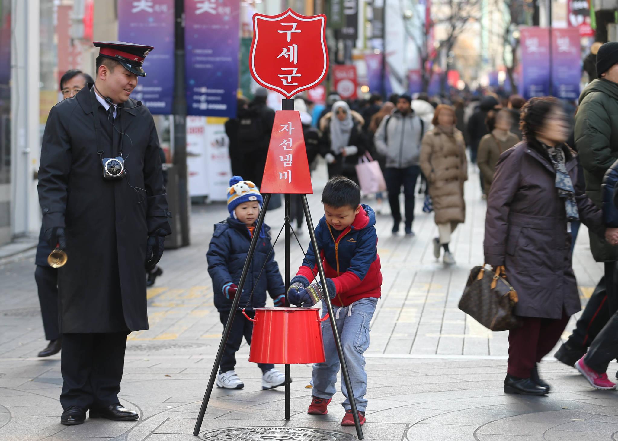 서울 명동거리 구세군 자선냄비에 형제가 함깨 성금을 넣고 있다. 신인섭 기자