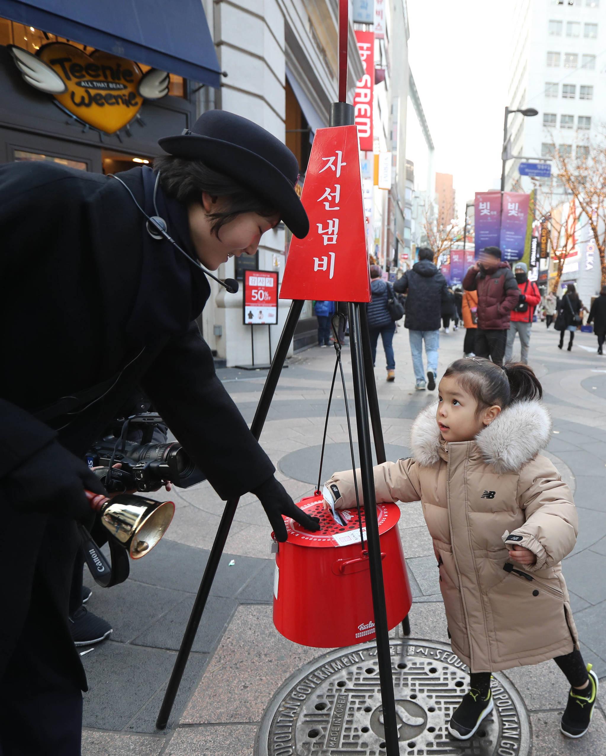 서울 명동거리에서 한 어린이가 자선냄비에 성금을 넣고 있다. 신인섭 기자