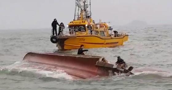 해경 대원들이 3일 오전 6시 12분쯤 인천 영흥도 인근 해상에서 전복된 낚싯배에 타고 있던 실종자들을 수색하고 있다. 전복된 낚싯배의 모습. [연합뉴스]