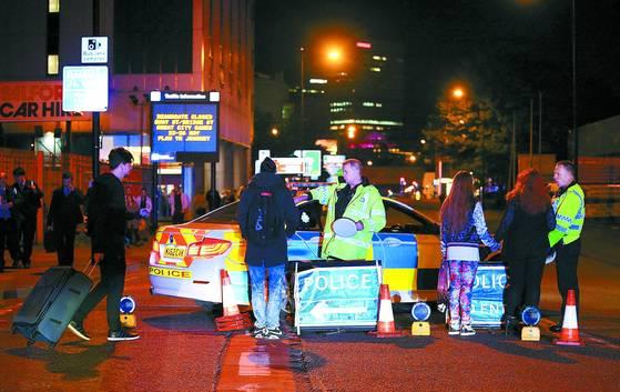 지난 5월 영국 경찰들이 테러가 벌어진 맨체스터 아레나에 출동해 콘서트장에서 나온 청소년들을 대피시키고 있다. [AP=연합뉴스]