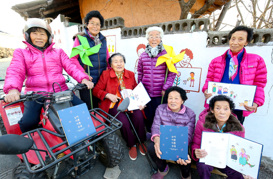 『눈이 사뿐사뿐 오네』를 펴낸 전남 곡성군 입면 할머니들이 6일 자신들의 모습이 그려진 마을' 길작은도서관' 담벼락에서 책을 들어보이고 있다. 프리랜서 장정필