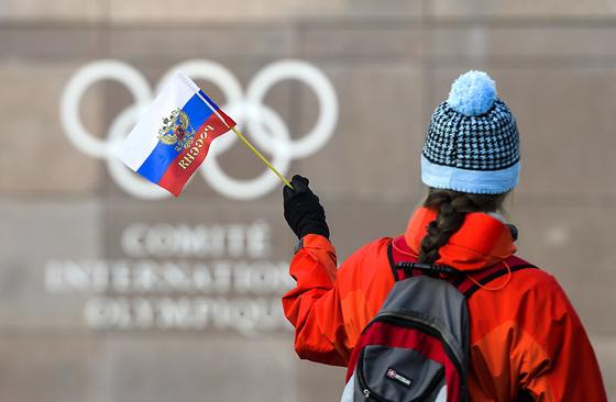 한 여성이 지난 5일 스위스 로잔의 IOC 본부 앞에서 러시아 국기를 흔들고 있다. [AP=연합뉴스]