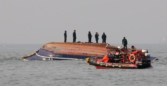 3일 오전 6시12분께 인천 영흥도 앞 해상에서 22명이 탄 낚싯배가 전복됐다. 사고선박 주변에서 해경이 헬기와 구조선을 이용해 구조 작업을 하고 있다. 낚싯배는 급유선과 충돌 후 전복됐다. [뉴스1]