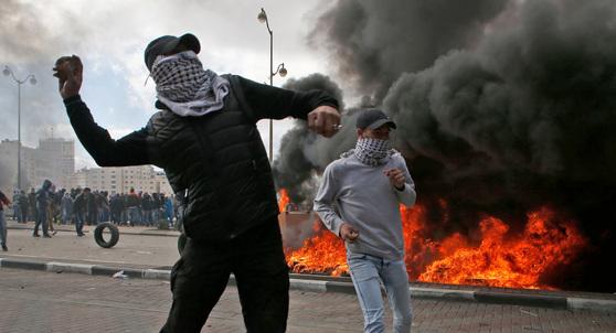 트럼프 대통령의 예루살렘 선언에 반발하는 팔레스타인 시위대가 7일(현지시간) 서안지구 라말라에서 돌을 던지며 시위를 하고 있다. 이스라엘군은 서안에 수백 명의 병력을 추가 배치했다. [AFP=연합뉴스]