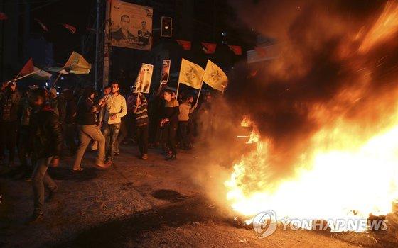 팔레스타인 국기와 야세르 아라파트 전 팔레스타인 자치정부 수반 사진을 든 사람들이 가자시티에서 시위를 벌이며 타이어를 불태우고 있다. [AP=연합뉴스]