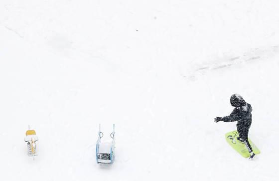 강원 대부분 지역으로 대설주의보가 확대된 10일 춘천시 우두동 한 놀이터에서 어린이가 눈썰매를 타고 있다.[연합뉴스]