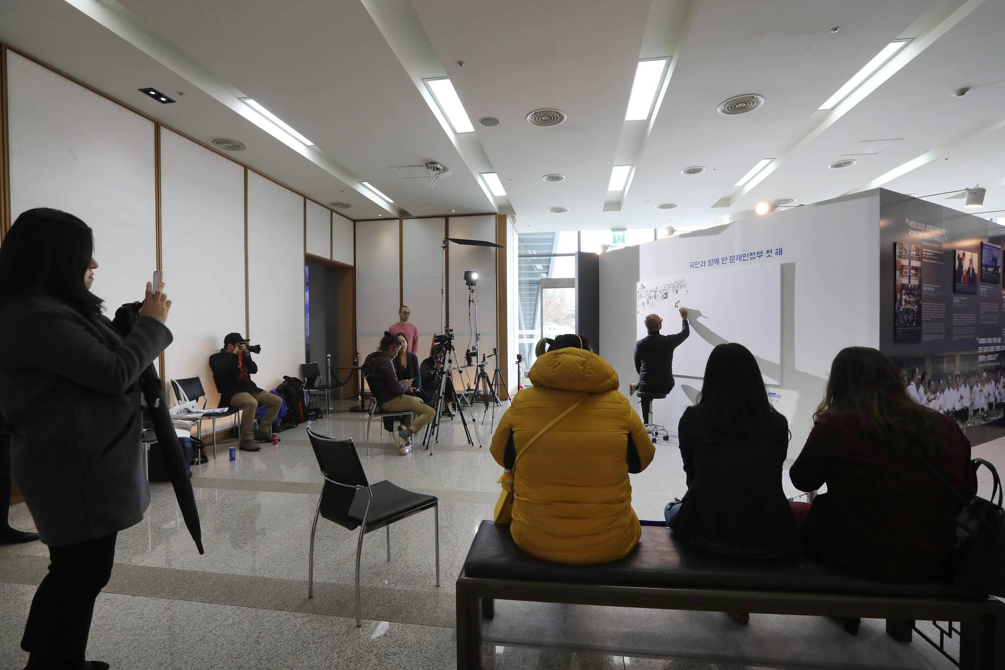김정기 작가가 대형 보드에 그림을 그리는 라이브 드로잉쇼를 관람객들이 보고 있다. 신인섭 기자