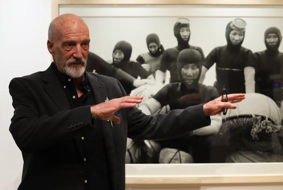 전설의 비주얼 스토리텔러 데이비드 앨런 하비가 8일 뉴욕에서 열린 제주 해녀 사진전에서 작품 사진에 대해 설명하고 있다. [최정 JTBC 기자]