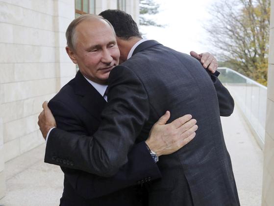 지난달 20일(현지시간) 러시아 소치를 깜짝 방문한 바샤르 알 아사드 시리아 대통령을 포옹하며 환대하고 있는 블라디미르 푸틴 러시아 대통령(왼쪽). [AP=연합뉴스]