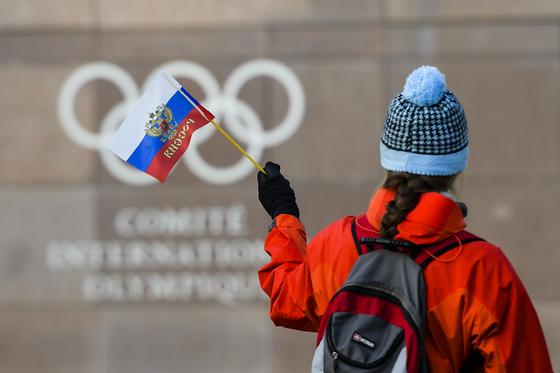 6일 스위스 로잔 IOC 본부 앞에서 한 여성이 러시아 국기를 흔들고 있다. IOC는 이날 러시아의 평창올림픽 참가 불허를 결정했다. [로잔 AP=연합뉴스]