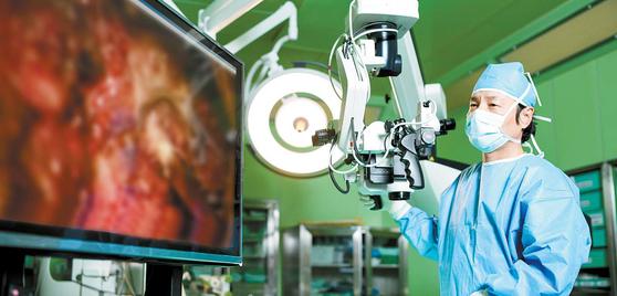 이영상 척추센터장이 60대 퇴행성 척추전방전위증 환자에게 현미경 수술을 하고 있다. 환자 몸에 구조물을 넣지 않고 최소한의 수술로 통증을 없애는 것이 치료의 최우선 목표다. 김동하 기자